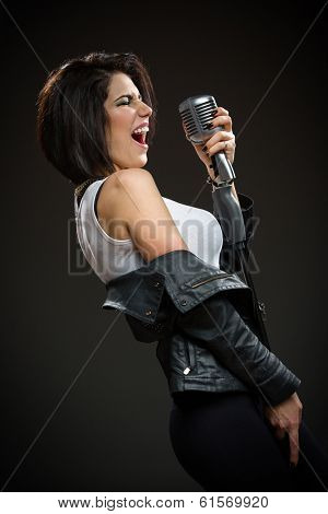 Side view of female rock singer wearing black jacket and keeping mic on grey background. Concept of music and rave