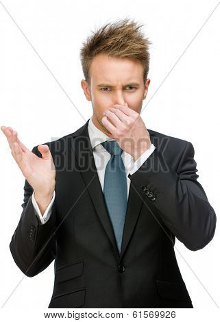 Half-length portrait of businessman covering his nose, isolated on white. Concept of stink and disgust