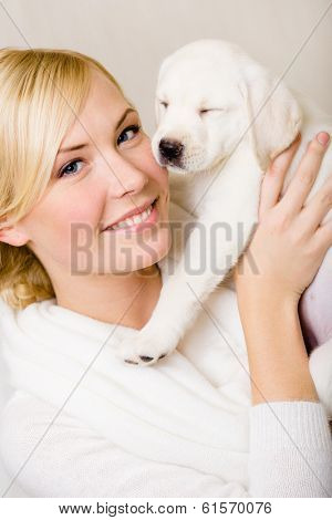 Woman keeping white puppy of Labrador with eyes shut near her face