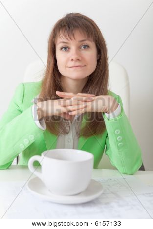 Young Woman Sits At Table With Big Cup Of Coffee