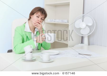 Tired Woman Sits At Table With Big Cup Of Coffee And Yawns