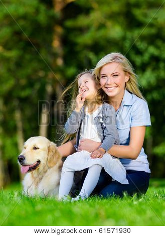 Mother and daughter with dog sitting on the green grass at the summer park