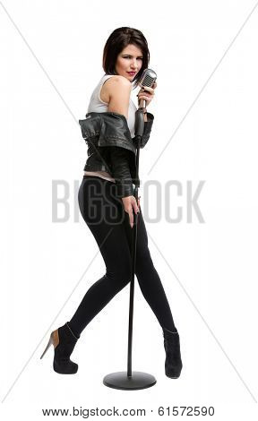 Full-length portrait of rock musician wearing leather jacket and keeping static mic, isolated on white. Concept of rock music and rave