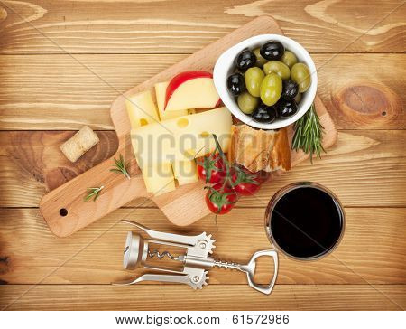 Red wine with cheese, bread, olives and spices. Over wooden table background. View from above