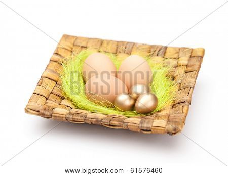 Brown and golden easter eggs are on wattled plate with sisal green fibre, isolated on white background