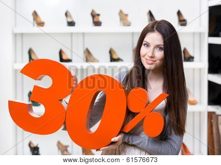 Woman keeps the model of 30% sale on shoes standing at the shopping center against the showcase with pumps