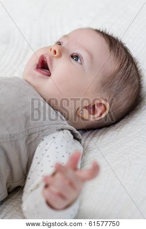 Happy baby girl lying on back over white bedcover