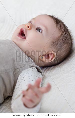 Happy baby girl lying on back over white bedcover