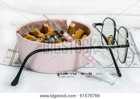 Ashtray, Syringe, Glasses And Other Stress Object From Work On White Blueprint Background