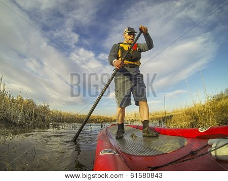 mature male paddler enjoying workout on an inflatable stand up paddleboard (SUP), calm lake in one of nature areas in Fort Collins, Colorado,  distorted wide angle view