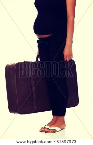 Pregnant woman with old suitcase