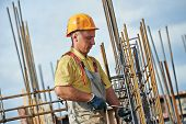 stock photo of concrete pouring  - builder worker knitting metal rods bars into framework reinforcement for concrete pouring at construction site - JPG
