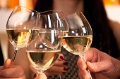 foto of sparkling wine  - Clinking glasses with white wine and toasting - JPG