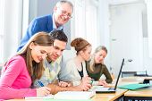 stock photo of supervision  - Group of students learning at college supervised by professor - JPG