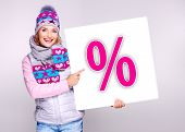 stock photo of outerwear  - Adult smiling woman in warm outerwear holds the white banner with percent symbol on it - JPG