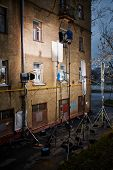 Professional lighting equipment - floodlights, reflecting screens - mounted near old house wall
