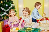 foto of tangerine-tree  - Three children sit in room under christmas tree among gift boxes and wicker baskets full of tangerins - JPG