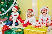 Three children in santa caps sit on furry rug under decorated christmas tree poster