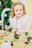 Smiling little girl dressed in furry mantle sits at wooden table and paints revealed pine-cone with