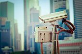 picture of cctv  - Vintage retro hipster style travel image of CCTV surveillance camera in Singapore with skyscapers in background - JPG