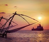 Vintage retro hipster style travel image of Kochi chinese fishnets on sunset and modern ship. Fort K