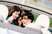 picture of turn-up  - Two happy girls sitting in the car and thumbing up look back and have fun while having little car trip - JPG