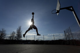 pic of slam  - Silhouette of a male basketball player in mid air about to slam dunk the ball with the sun creating a flare effect - JPG
