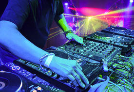 stock photo of disc jockey  - Dj mixes the track in the nightclub at party. In the background laser light show