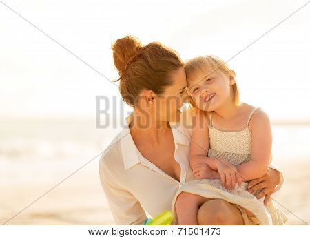 Portrait Of Happy Mother And Baby Girl On The Beach In The Eveni