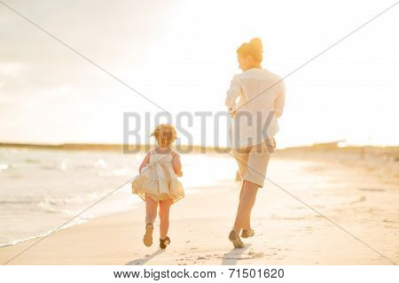 Mother And Baby Girl Running On The Beach In The Evening. Rear View