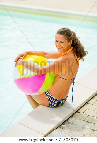 Portrait Of Smiling Young Woman With Ball Sitting Near Swimming Pool