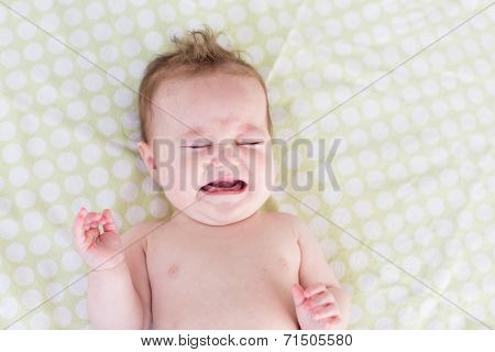 Little Crying Newborn Baby On A Green Blanket