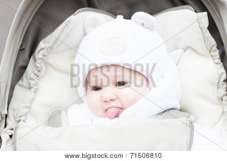 Funny Little Baby In A Teddy Bear Hat Showing Its Tong Sitting In A Stroller On A Cold Winter Day