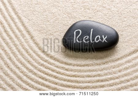 A black stone with the inscription Relax