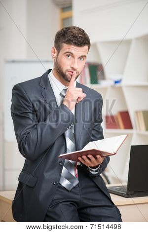 Portrait of handsome confident businessman in office interior ho