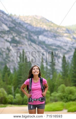 Hiking woman looking up at copy space in Yosemite looking at mountain forest landscape in Yosemite National Park, California, USA. Happy multiracial young Asian Caucasian woman.