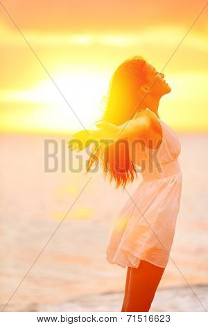 Freedom woman enjoying feeling happy free at beach at sunset. Beautiful serene relaxing woman in pure happiness and elated enjoyment with arms raised outstretched up. Asian Caucasian female model.