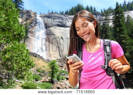 Smartphone - woman hiker using smart phone app on travel hike living healthy active lifestyle by waterfall in Yosemite National Park, California, USA.