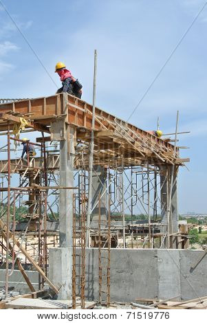 Construction workers fabricating beam reinforcement bar