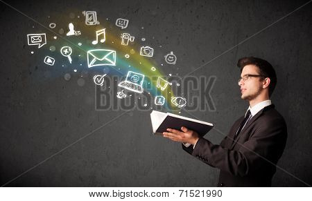 Businessman reading a book with multimedia icons coming out of the book