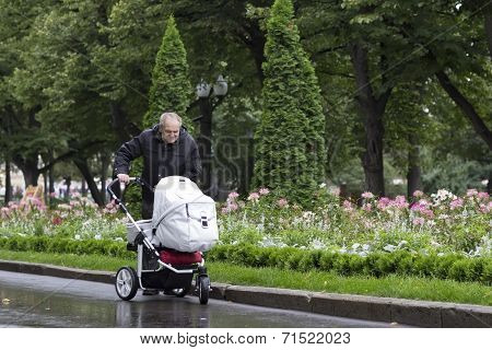 Great-grandfather Walking With A Stroller On A Cold Rainy Day In A Beautiful Park