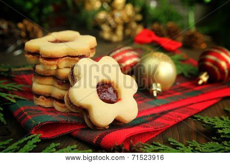 Christmas cookies with flowers shape on a wooden table with christmas balls and cedar branch