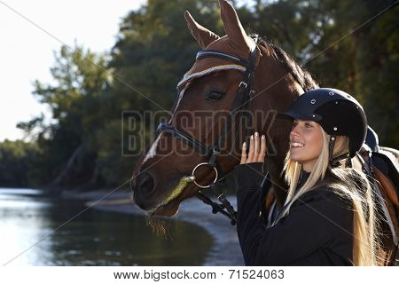 Riverside portrait of happy female rider and beautiful horse.
