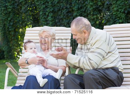 Grandparents Playing With A Little Baby In The Garden