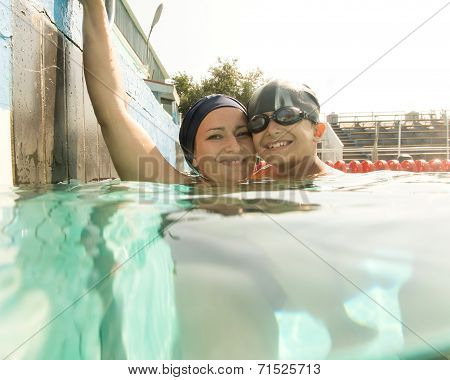 Mom giving son a swimming lesson in pool during summer