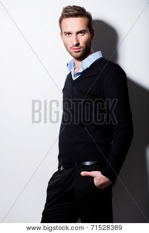 Fashion portrait of young man in black pullover and blue shirt with contrast shadows.