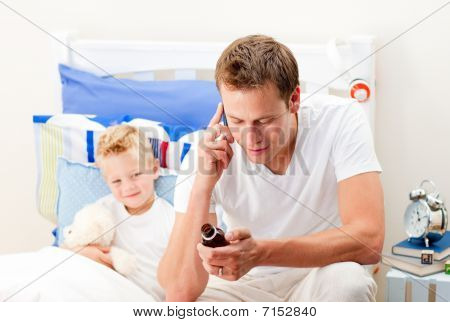 Attentive Man Looking After His Sick Son