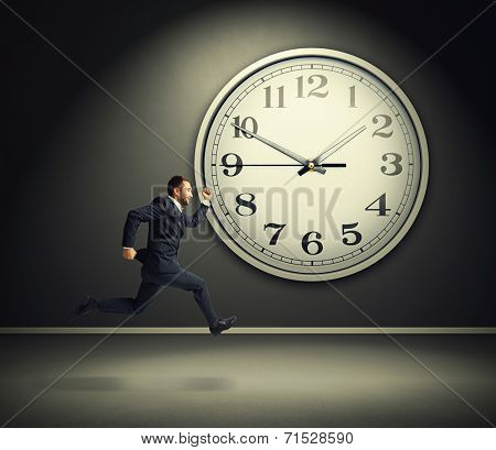 smiley running businessman and big white clock in dark room