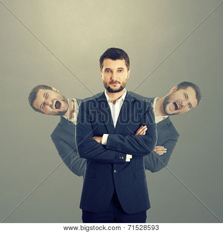 two screaming men behind confident businessman in suit over dark background