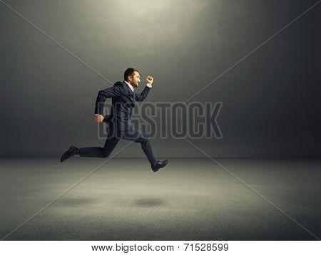 happy businessman in formal wear running over dark background